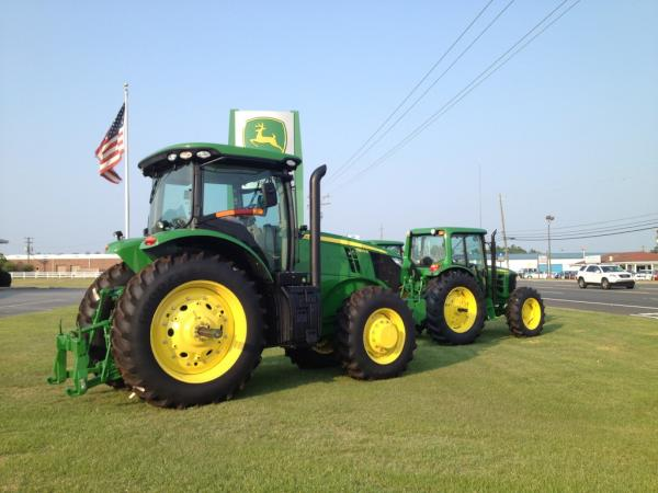 John Deere tractor at dealership with flag