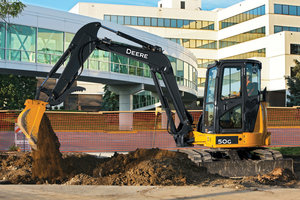 John Deere compact excavator operators can now switch buckets without leaving the cab thanks to the new hydraulic coupler.