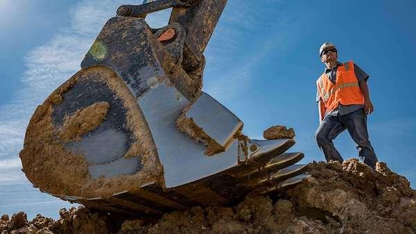 "<img src=""MiCa Enterprises.jpg"" alt=""Man standing next to excavator bucket"">"